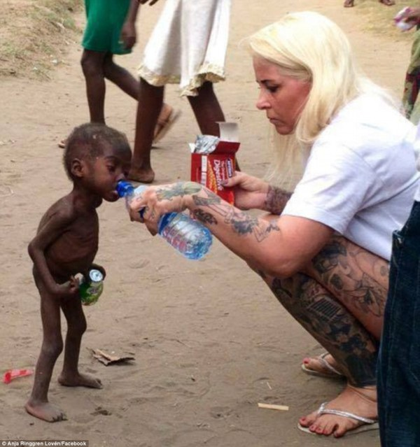 Aid worker giving water to a starving Nigerian boy.