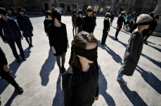 Romanian women activists stand blindfolded with black scarves during a performance honoring the history of feminist movements, marking the International Women's Day in Bucharest, Romania, Tuesday, March 8, 2016. (AP Photo/Andreea Alexandru) ROMANIA OUT