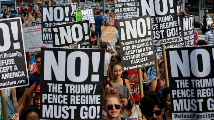 Protesters with signs saying NO! The Trump/Pence Regime Must Go!